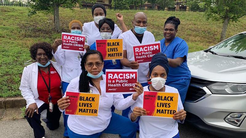 """Nurses hold signs """"Black Lives Matter"""""""