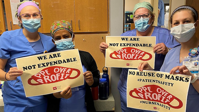 Nurses hold signs calling for PPE