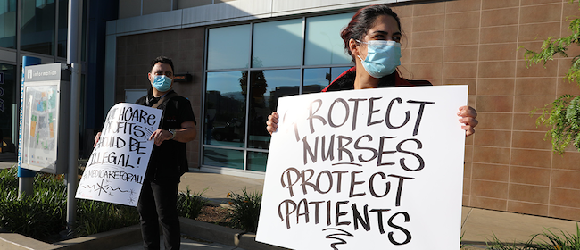 "Nurses hold signs ""Protect Nurses, Protect Patients"""
