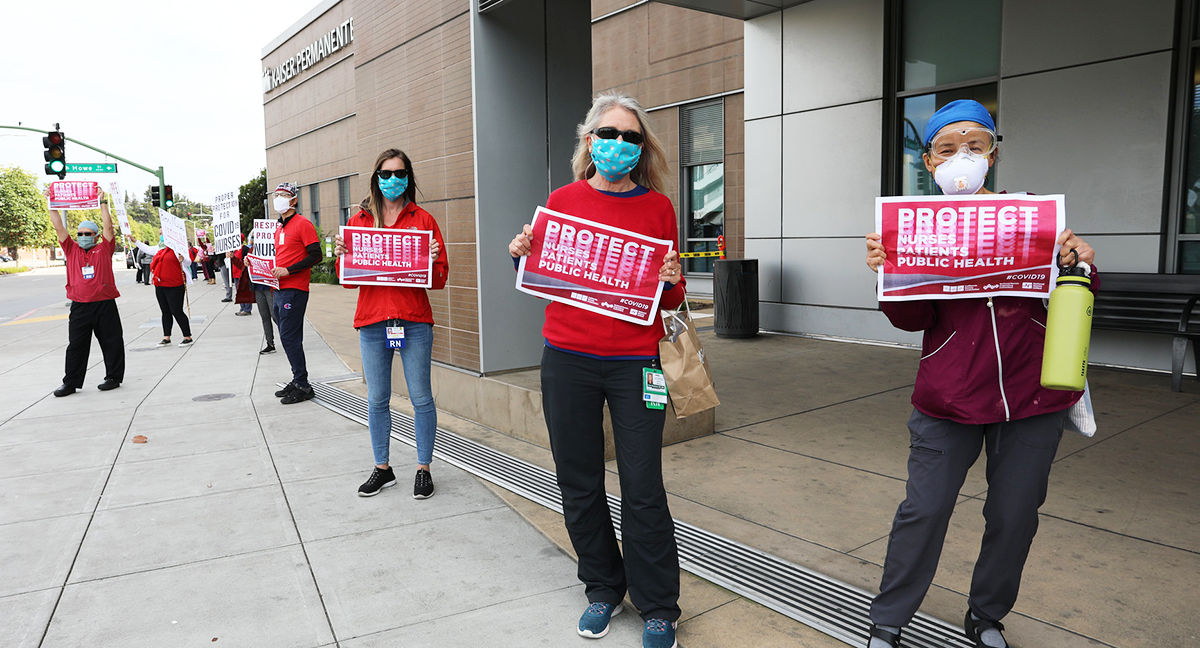 "Nurses outside hospital hold signs ""Protect Nurses, Patients, Public Health"""
