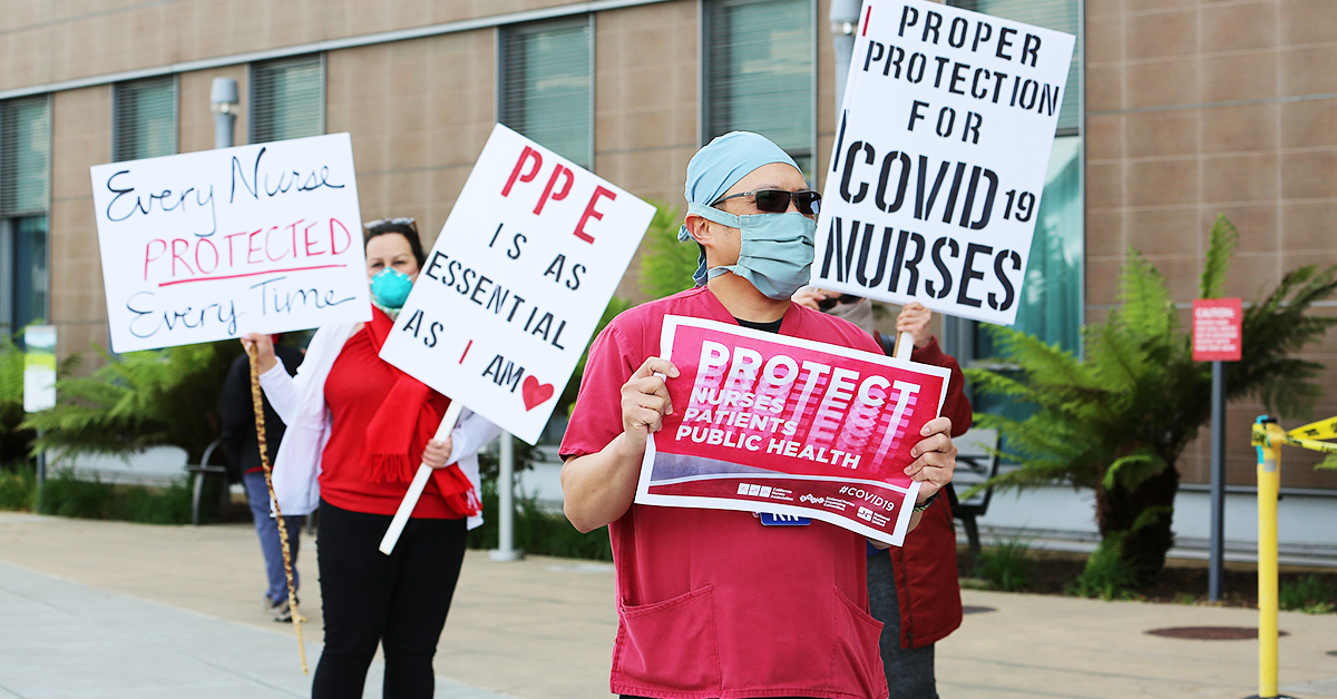 "Nurses protesting for PPE holding signs ""PPE is as essential as I am"", ""Proper protection for Covid-19 Nurses"", ""Every Nurse Protected Every Time"", ""Protect Nurses, Patients, Public Health"""