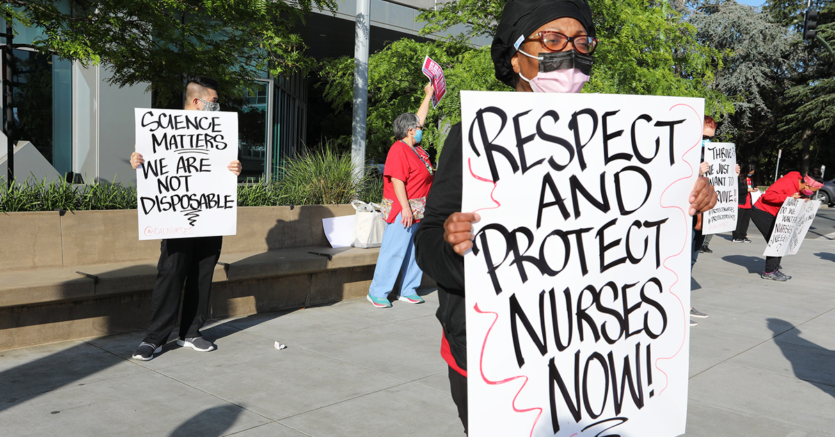 "Nurses outside facility with signs ""Respect and protect nurses now!"" and ""Science matters, we are not disposable"""