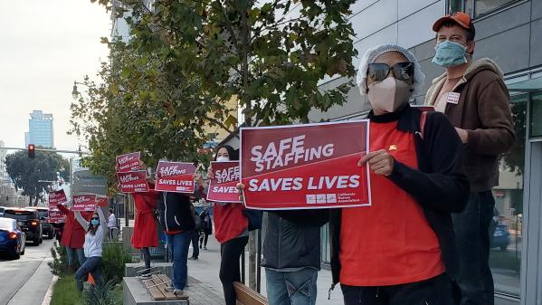 Nurses hold signs calling for safe staffing
