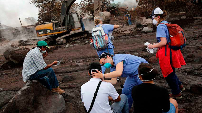 Nurses treat the eyes of people who continue to search for the remains of family members near Fuego volcano in Escuintla, Guatemala, in 2018