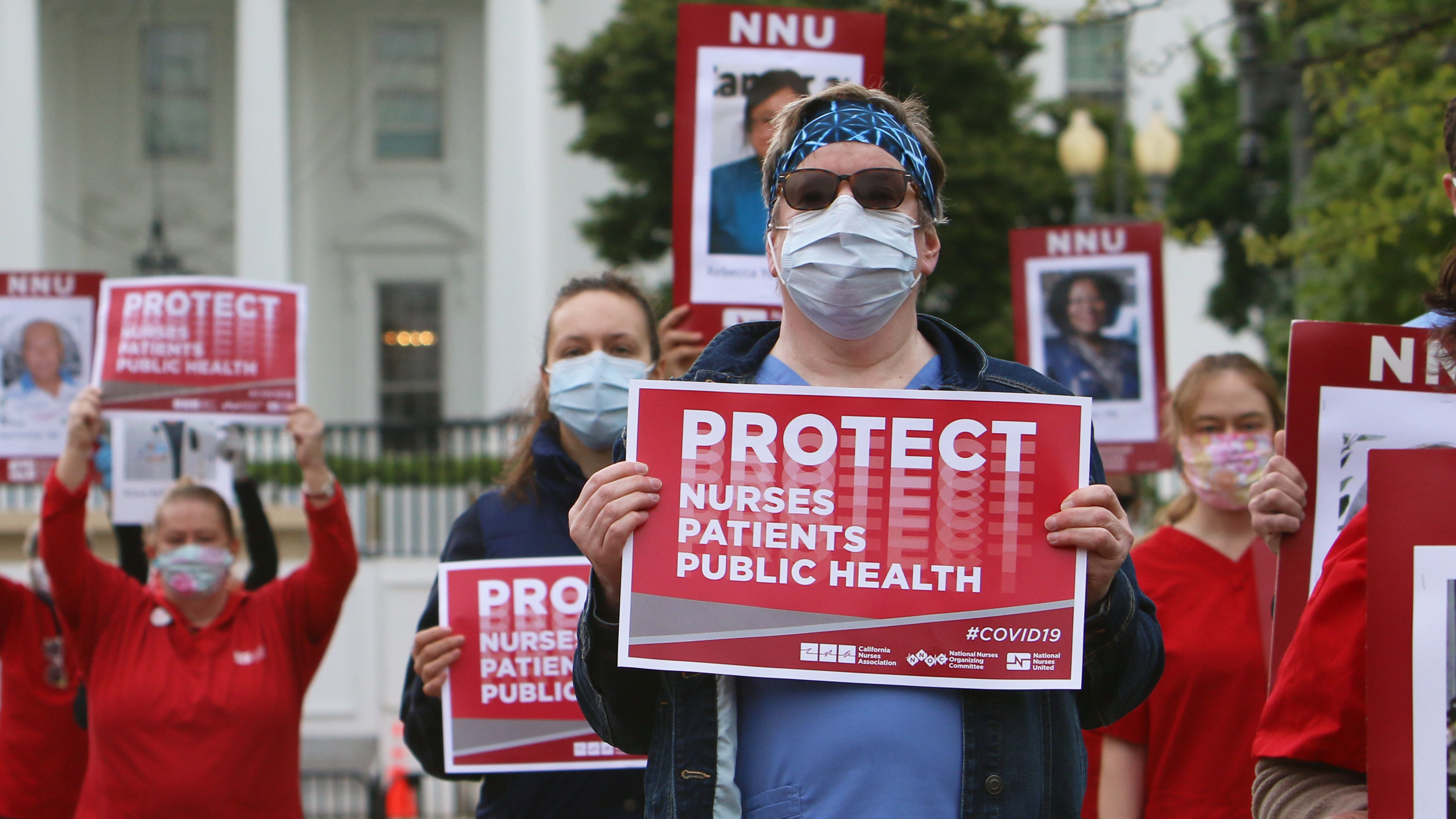 "Nurses hold ""Protect Nurses"" signs outside the Whitehouse"