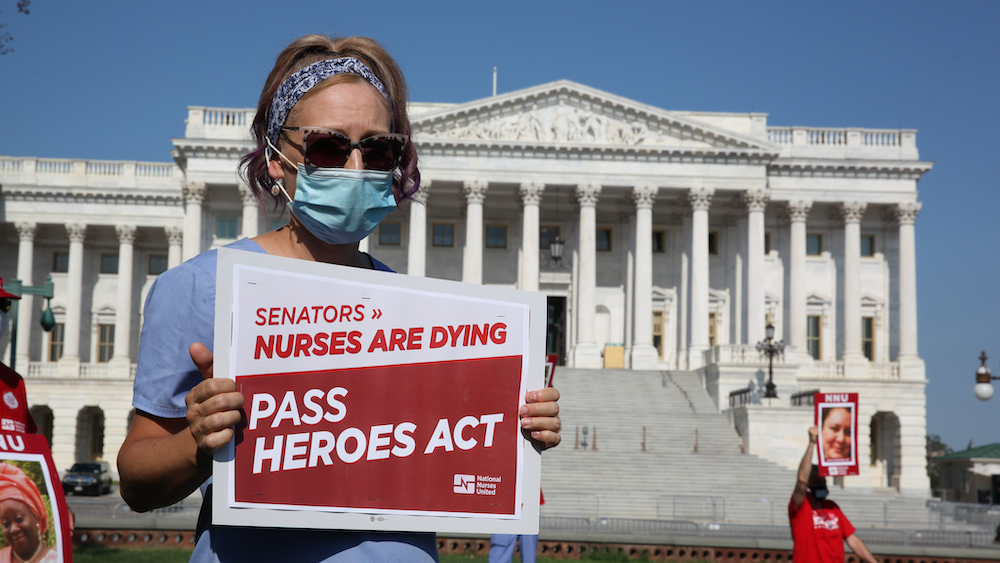 "Nurse holds sign outside U.S. Senate ""Pass HEROES Act"""