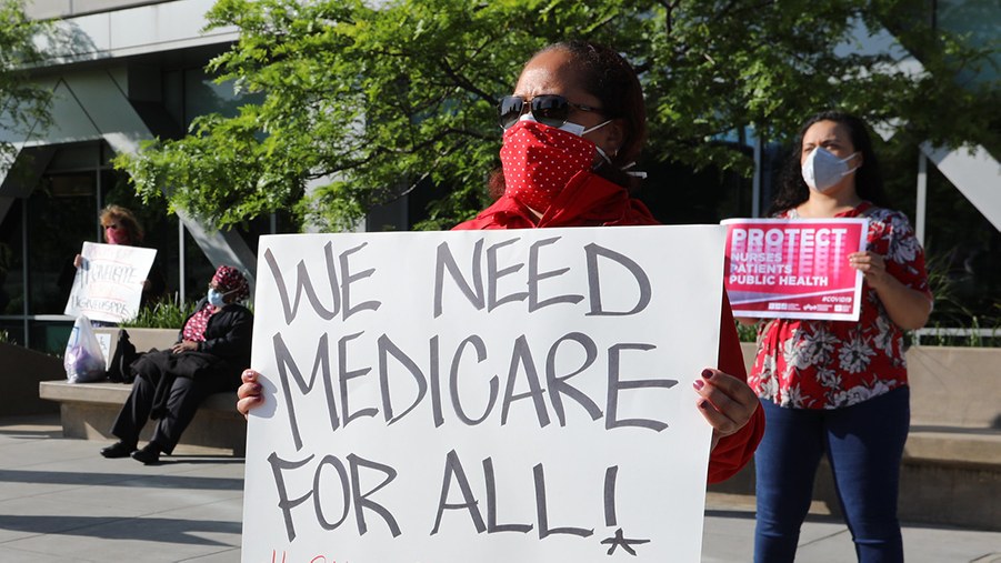 "Nurse holds sign ""We need Medicare for All"""