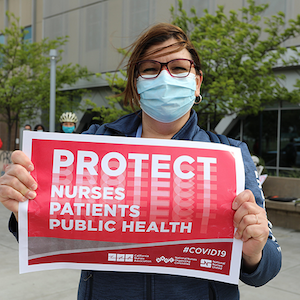 "Nurse holds sign ""Protect Nurses, Patients, Public Health"""