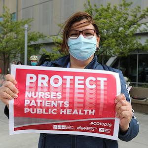 """Nurse holds sign """"Protect Nurses, Patients, Public Health"""""""