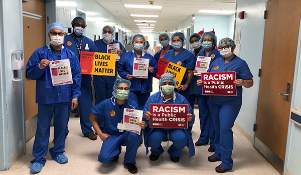 Nursews hold signs calling for racial justice