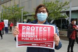 """Nurse holds sign """"Protect Nurses, Patients, Public Safety"""""""