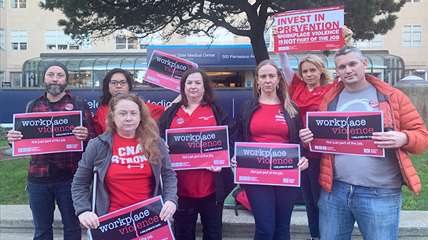 Nurses hold signs calling for Workplace Violence Prevention
