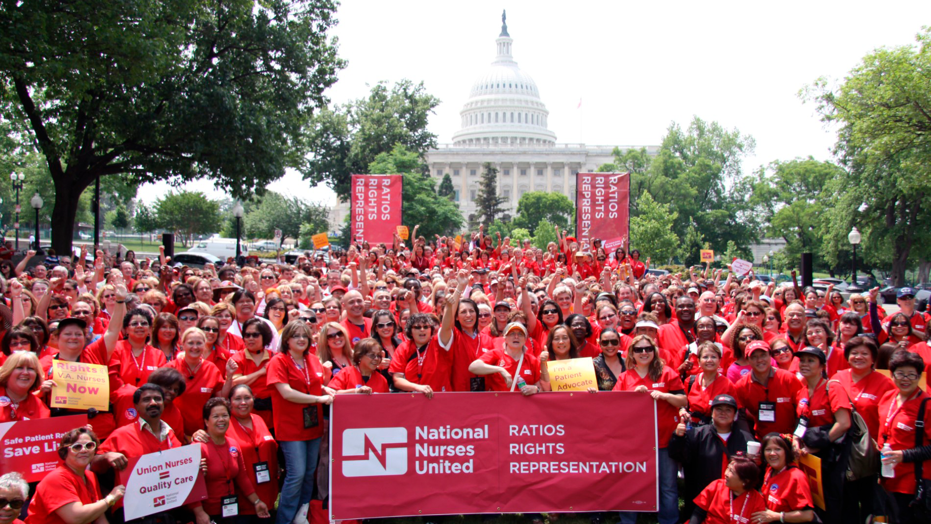 """Large crowd of nurses hold sign """"Ratios, Rights, Representation"""" at state capitol building."""
