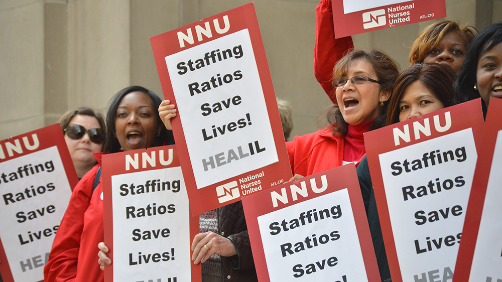 "Nurses hold signs: ""Staffing Ratios Save Lives!"""