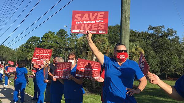 """Nurse holds sign """"Safe Staffing Now"""""""