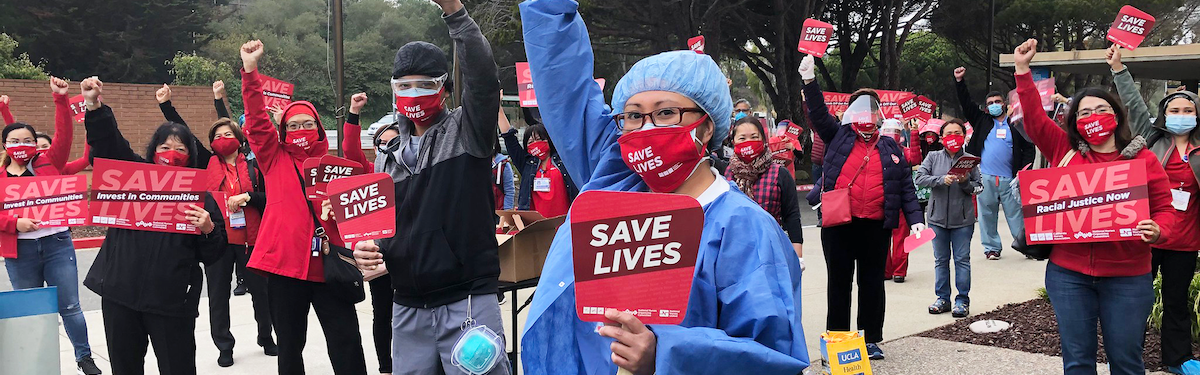 "Nurses hold signs ""Save Lives"""