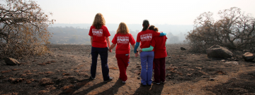 Nurses stand looking at remains of fire