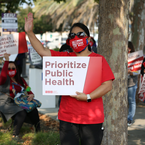 "Nurse holds signs ""Prioritize Public Health"""