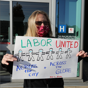 "Nurse holds sign ""Labor United"""