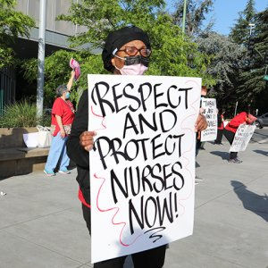 "Nurse outside facility with sign ""Respect and protect nurses now!"""