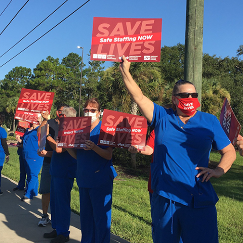 Nurses hold signs calling for safe staffing