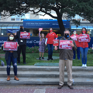 Nurses outside UCSF hospital hold signs calling for safe staffing