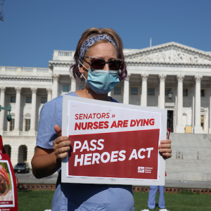 "Nurse holds sign ""Pass the HEROES Act"" outside U.S. Senate"