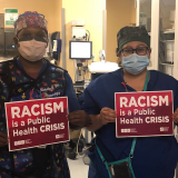 "Nurses hold signs ""Racism is a Public Health Crisis"""