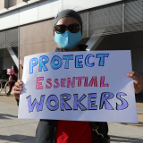 "Nurse holds sign ""Protect Essential Workers"""