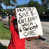 Nurse holds sign protesting HCA cost cutting measures