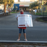 "Nurses hold ""COVID-19 checklist"" signs outside Fawcett Memorial"
