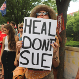"Woman holds sign ""Heal Don't Sue"""
