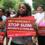 "Woman holds sign ""Stop suing patients and families"""