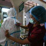 A nurse draws a smiley face on the back of a fellow health worker