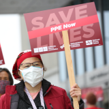 "Nurse holds sign ""Save Lives, PPE Now"""