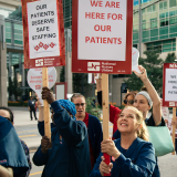 "Nurses hold signs ""We are here for our patients"""