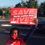 "Nurse holds sign ""Racial Justice Now"""