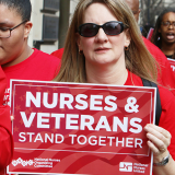 "Nurse holds sign ""Nurses and Veterans Stand Together"""